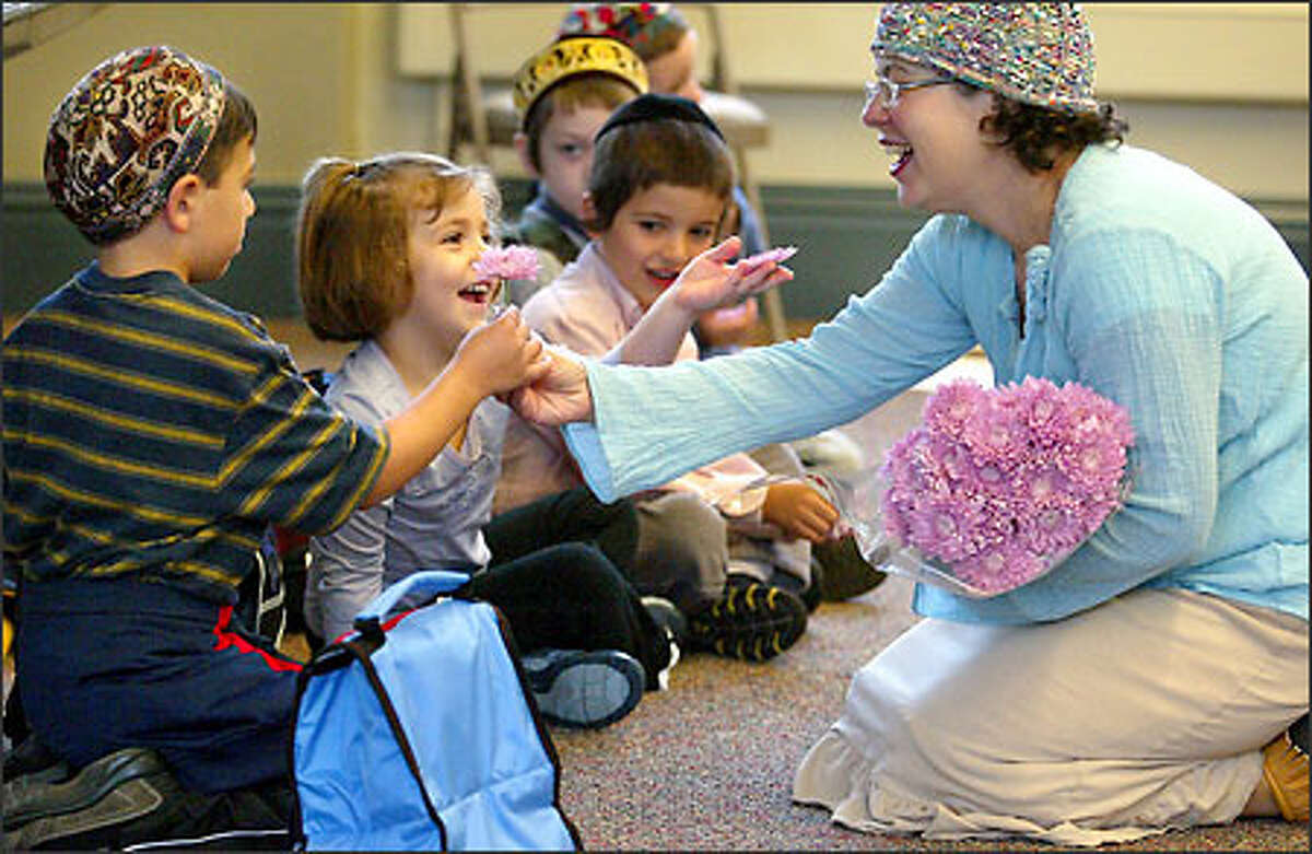 Leah Jacobsen hands out flowers to her kindergartners at the reopening of the Seattle Hebrew Academy. From left are Ophir Amon, Eva Goodman and Yitzy Levin