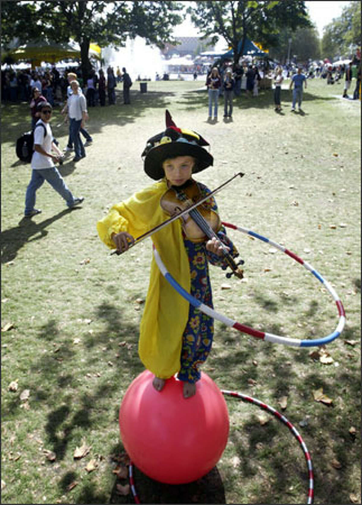Balancing on a rubber ball and twirling a hula hoop, 9-year-old Una Bennett plays the violin at Bumbershoot. She and her juggling brother, Ezra Weill, 12, can earn $200 to $300 a day.