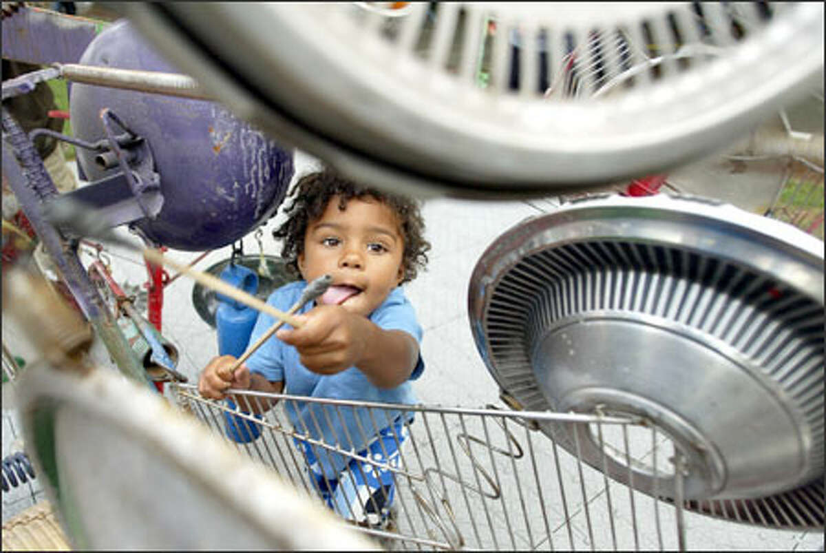 Habib Ceesay, 2, of Seattle pounds out a rhythm on hubcaps that are part of Ben Smith's interactive musical sculpture