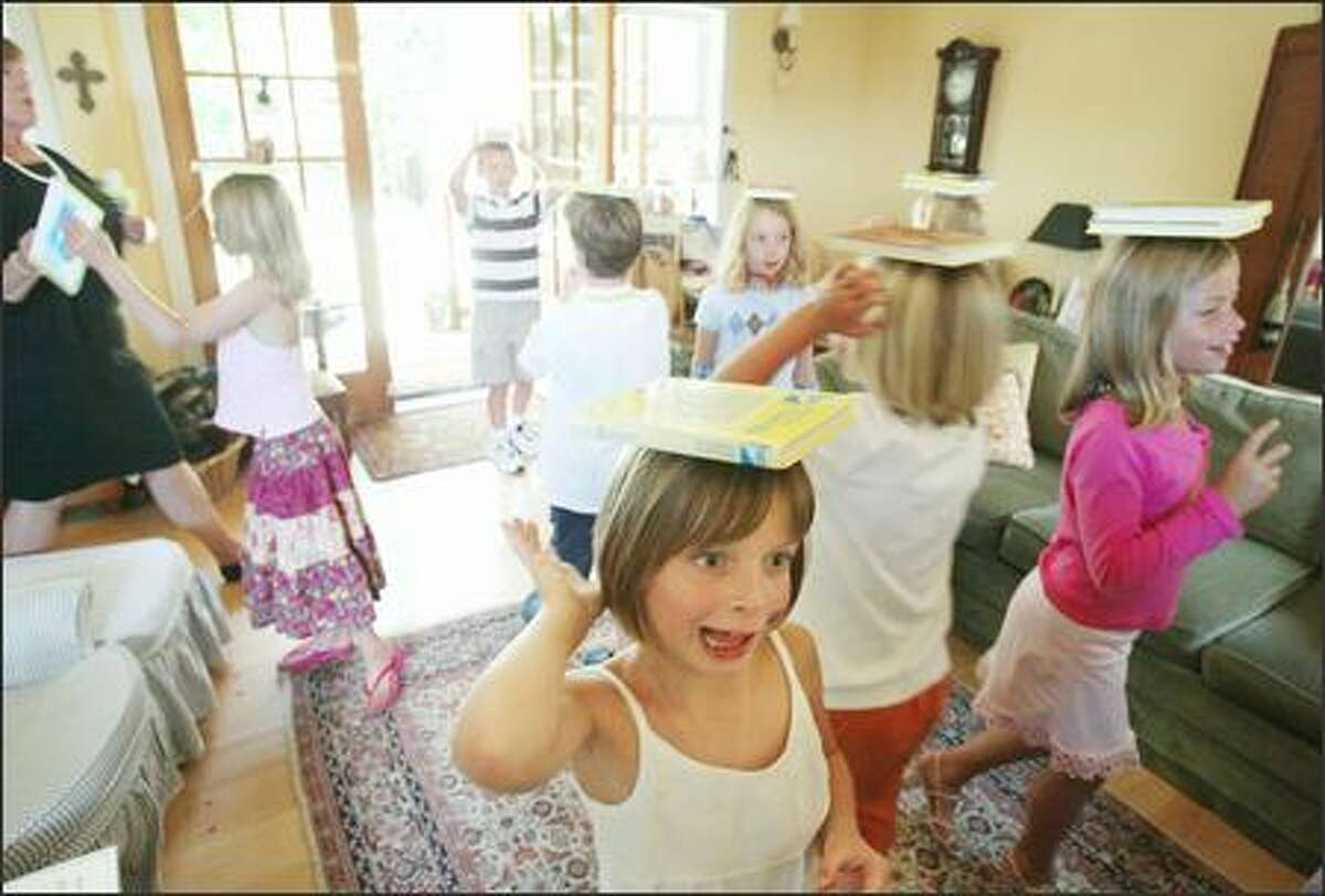 At Mrs. DeGroot's Wallingford Charm School, children walk with Nancy Drew books on their heads, aiming for statuesque posture. Frances Foody, 7, front, is about to lose her book as she heads toward her goal, a jar of candy. Dawn DeGroot is at the left.