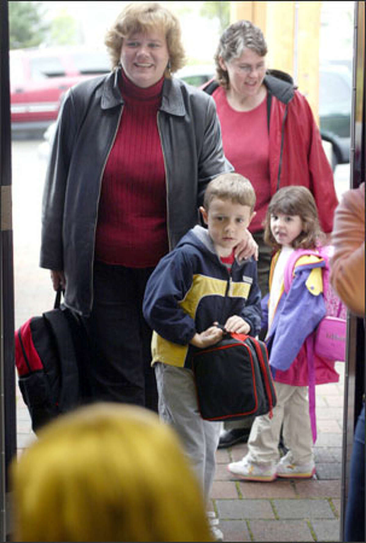 A little trepidation is apparent as Joseph Stryker confronts the first day of kindergarten with mom Tina at Soundview School in Lynnwood last Wednesday. Also making their way toward class are Susan Paish and daughter Megan.
