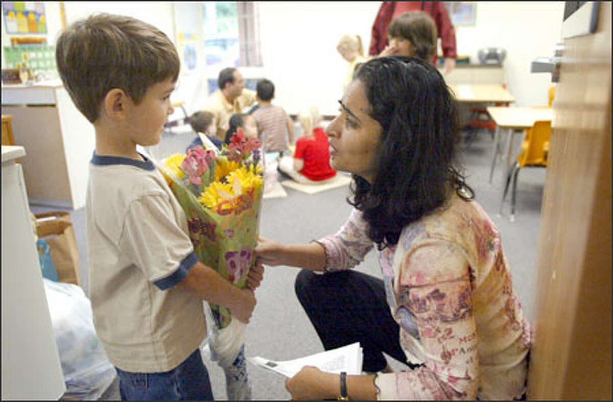 Nathan Sinclair, 4, a junior kindergartner at Soundview School in Lynnwood, brings teacher Neena Mathew a first-day present last Wednesday.