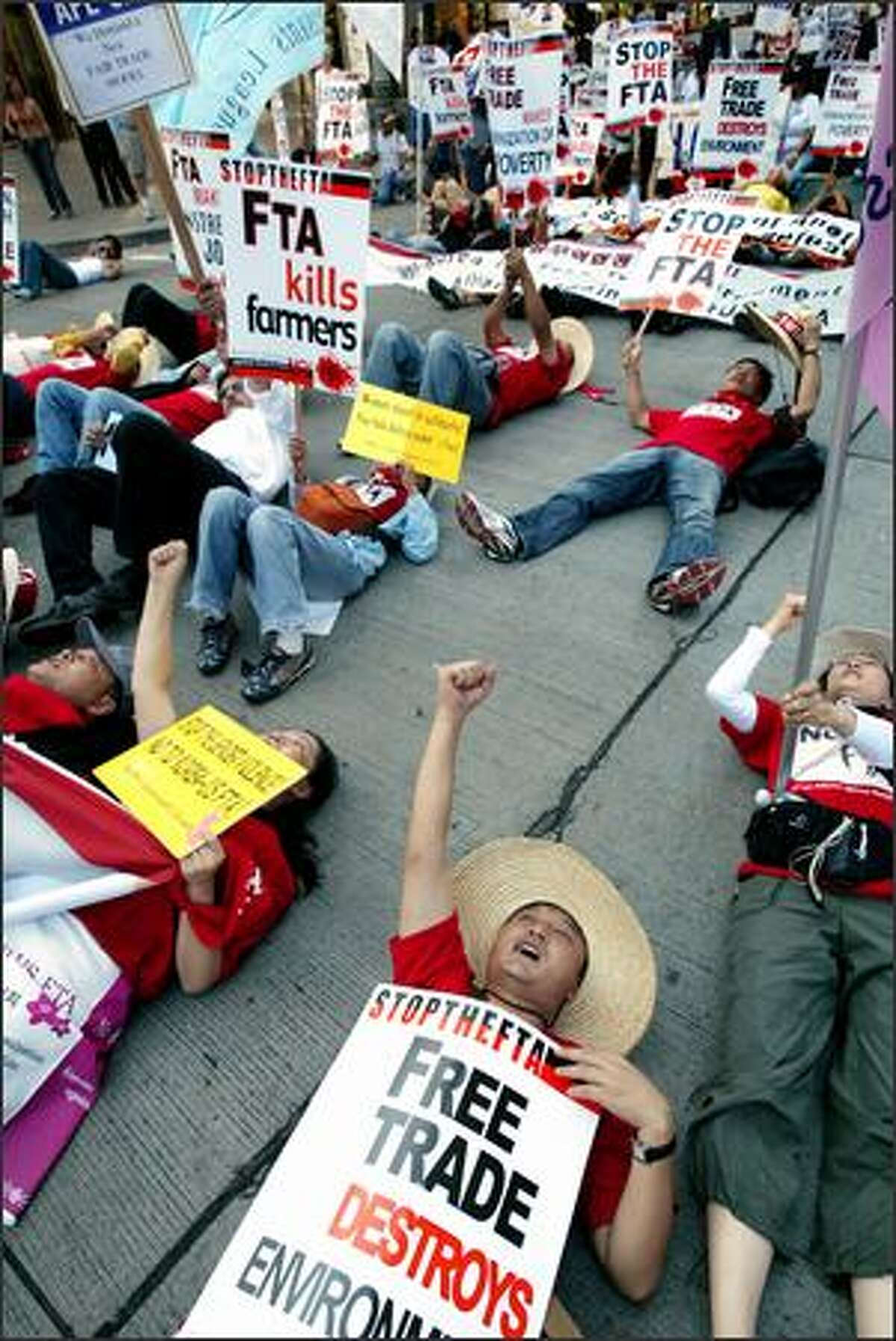 South Korean workers lie in the street in downtown Seattle while leading American union members in a two-hour lunchtime march Wednesday. The group, numbering about 1,000, was protesting negotiations that began Wednesday at the Washington State Convention and Trade Center toward a Korea-U.S. Free Trade Agreement. No violence was reported.