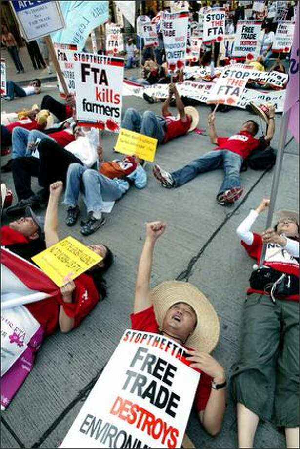 South Korean workers lie in the street in downtown Seattle while leading American union members in a two-hour lunchtime march Wednesday. The group, numbering about 1,000, was protesting negotiations that began Wednesday at the Washington State Convention and Trade Center toward a Korea-U.S. Free Trade Agreement. No violence was reported. Photo: Dan DeLong, Seattle Post-Intelligencer / Seattle Post-Intelligencer