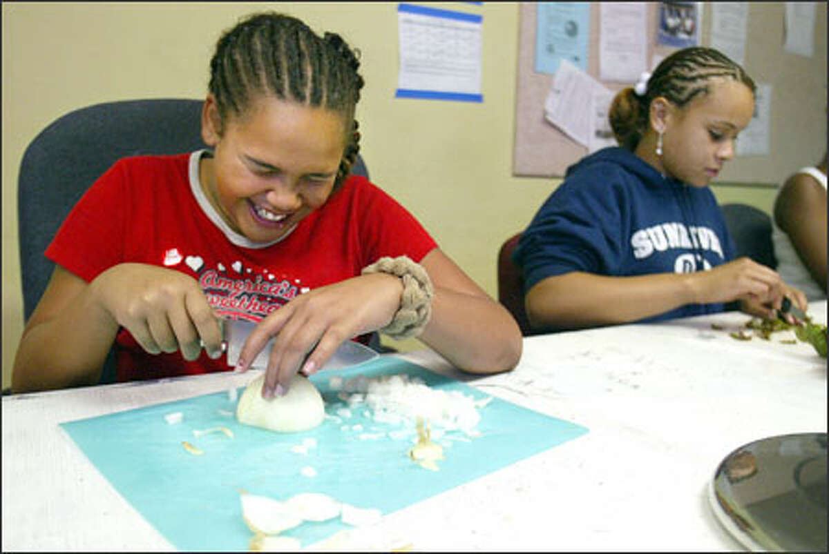 Mariah Williams, left, laughs -- and cries -- as she chops onions and Amari Ray cuts chard as they fix healthy meals in a King County S.N.A.C. class.