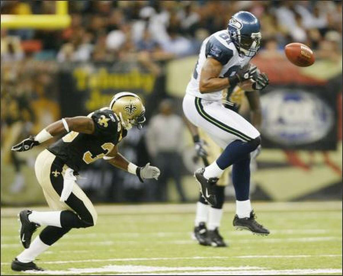 Koren Robinson drops a pass from Matt Hasselbeck as Saints' Ashley Ambrose closes in during the fourth quarter.
