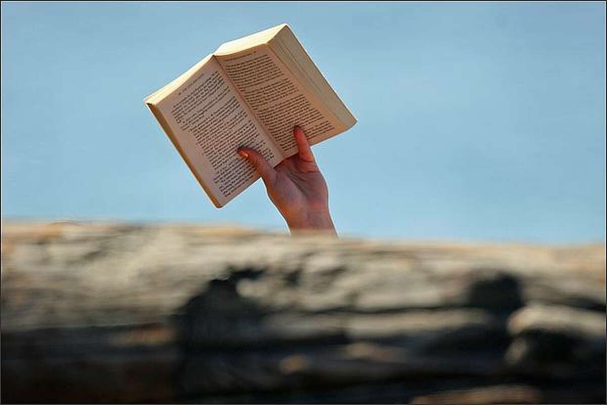 A sunbather reads a paperback in the afternoon sunlight at Golden Gardens Park in Ballard on Tuesday, September 9, 2008. (Mike Kane/Seattle P-I)