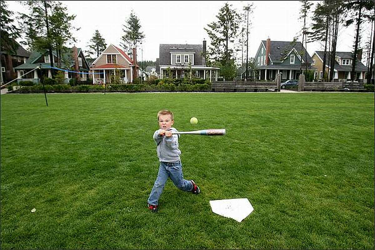 Three-year-old Cooper Young of Woodinville connects on a pitch from his mother, Jenni Young, while playing at Seabrook's Crescent Park in Pacific Beach, Wash. The Youngs were renting a house in the new beach town. (Dan DeLong/Seattle P-I)