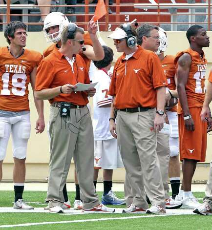 Texas' co-offensive coordinators Major Applewhite, front right, and Bryan Harsin,  front left, talk during the Texas Orange and White spring football scrimmage on Sunday, April 3, 2011, in Austin, Texas. The Orange team won 27-7. Photo: AP