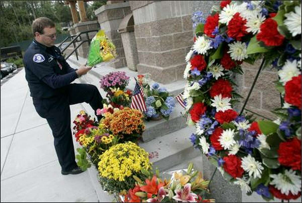 Off-duty Seattle firefighter Craig Keith of Brier arranges flowers brought by mourners Wednesday to an impromptu memorial outside the Brier Police Department at City Hall for Officer Edwanton Thomas, who died after responding to an emergency call at the home of the city's former mayor, Gary Starks.