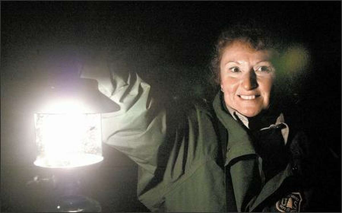 Debra Highsmith, a volunteer ranger with the U.S. Forest Service, lights the way with her lantern as she leads a tour of Ape Cave.