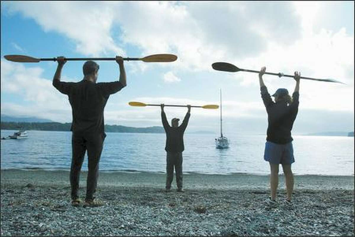 With Pelican Beach as his classroom, paddling instructor Chris Mitchell, center, gives Tom Marks and Barbara French a lesson in proper paddle grip and stroke techniques.