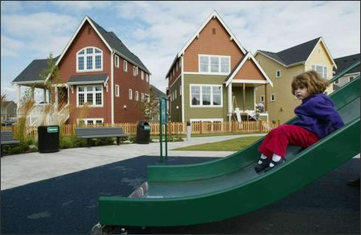 Ariana Kapocias, 3, enjoys a slide near new energy-efficient and environmentally friendly homes built by Lyle Homes in the High Point neighborhood in West Seattle. Ariana and her family moved into the neighborhood a month ago. Seattle's first Green Living Expo will showcase the homes this weekend and next.