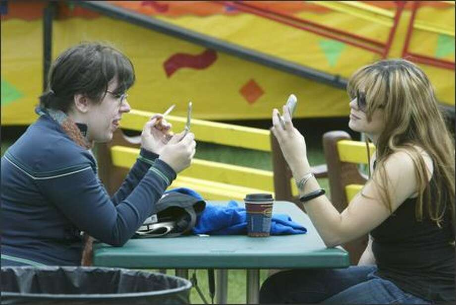 Urban hipsters Shae Allen, left, and Nicole Mallin check for text messages and voicemails during a smoke break while taking in Photo: Mike Urban, Seattle Post-Intelligencer / Seattle Post-Intelligencer