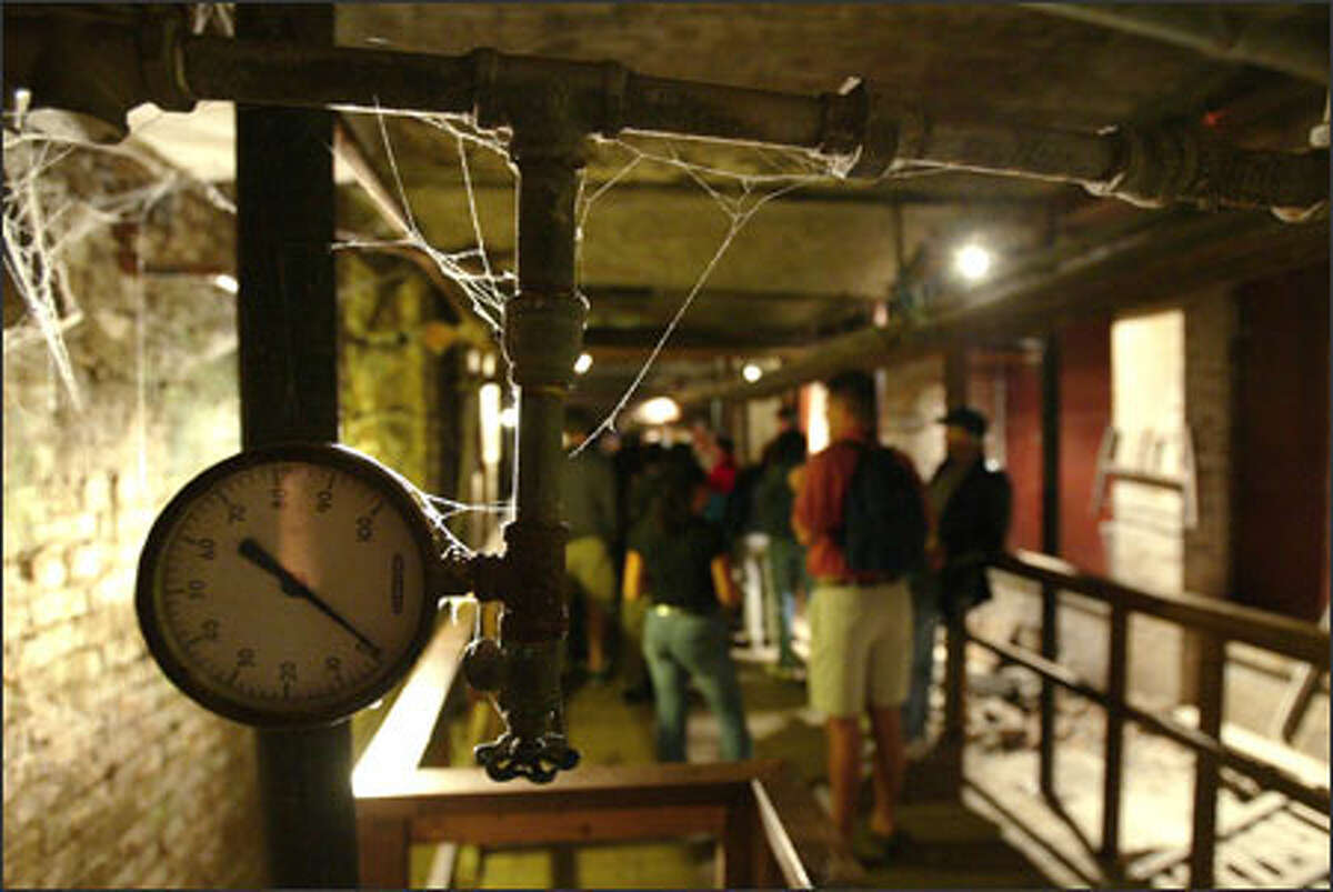 An old Seattle gauge can be seen sticking out of a wall as people take the Underground Tour in Pioneer Square on Sunday.
