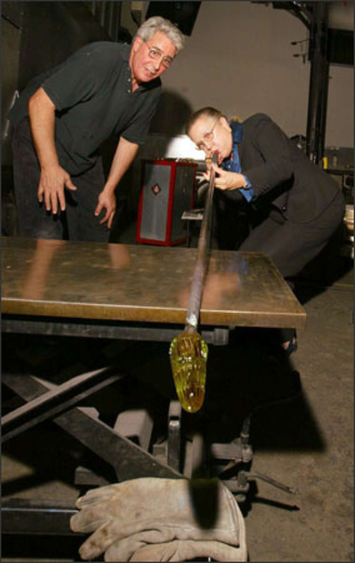 Seattle City Council President Jan Drago takes a turn at blowing glass. Drago, as Kenny Ramer, a glass-blowing assistant at Seattle Glassblowing Studio, looks on. Drago, who was facing Casey Corr in Tuesday's primary, had her election night party at the studio.
