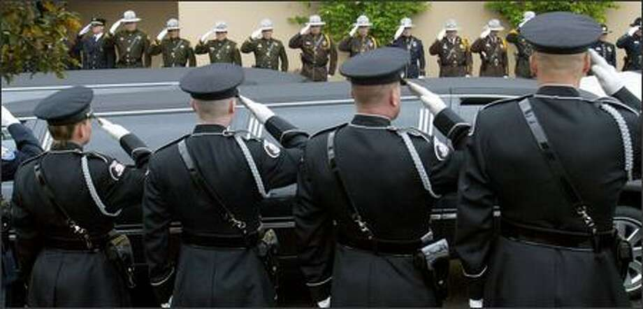 As officers salute, the hearse arrives at the memorial service for slain Brier Police Officer Eddie Thomas at the Westgate Chapel in Edmonds on Wednesday. Thomas died while responding to a medical emergency call at the home of former Brier Mayor Gary Starks. Cause of death is pending further investigation. Photo: Karen Ducey, Seattle Post-Intelligencer / Seattle Post-Intelligencer