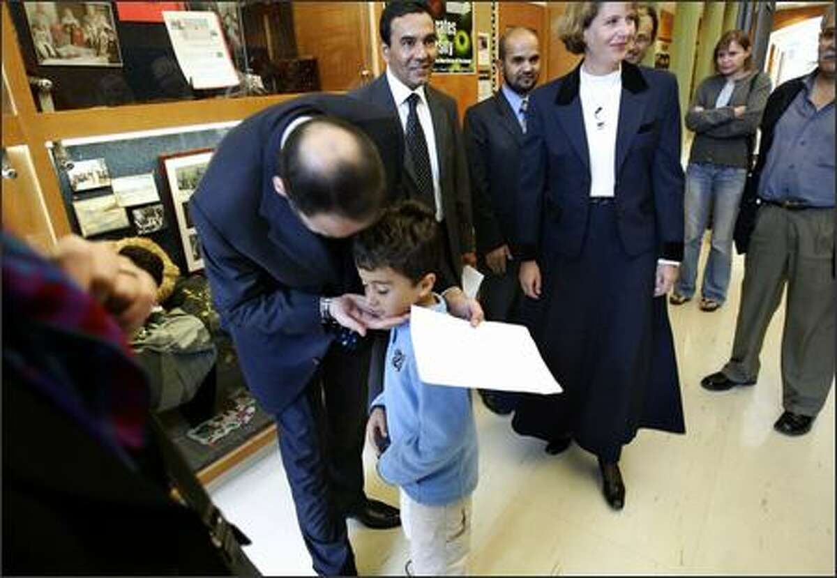 General Ata Mohammad Noor, governor of Balkh Province in Afghanistan, thanks Coe Elementary first-grader Zachary Harvey for a welcome card written in Farsi that he was given following an assembly at the Queen Anne school. Noor was there as part of a program to build schools in Afghanistan and promote exchanges between kids in both countries.