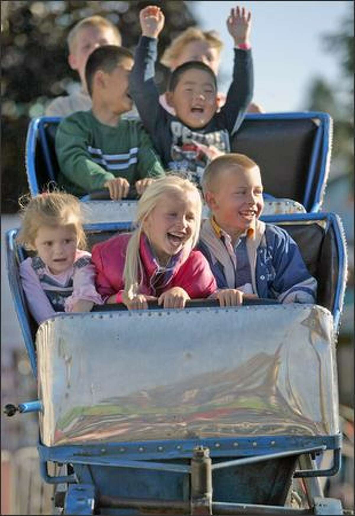 From left, Luccia Buck, 3, Abby Leaman 5, and Noah Leaman, 6, ride the little people's roller coaster at the Puyallup Fair earlier this week.