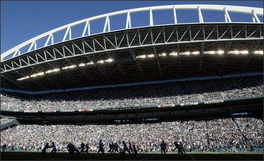 Much of the field at sold-out Qwest Field is covered in shadows during the fourth quarter of the Seattle Seahawks' 42-30 victory over the New York Giants last Sunday. Photo: Mike Urban, Seattle Post-Intelligencer / Seattle Post-Intelligencer