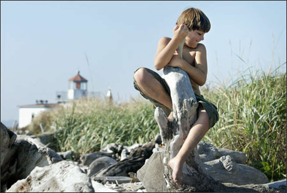 Eight-year-old Mario Barbaris of Magnolia plays among the driftwood near the West Point lighthouse. Mario was visiting the beach with his mother, Doreen Boehm. Photo: Dan DeLong, Seattle Post-Intelligencer / Seattle Post-Intelligencer
