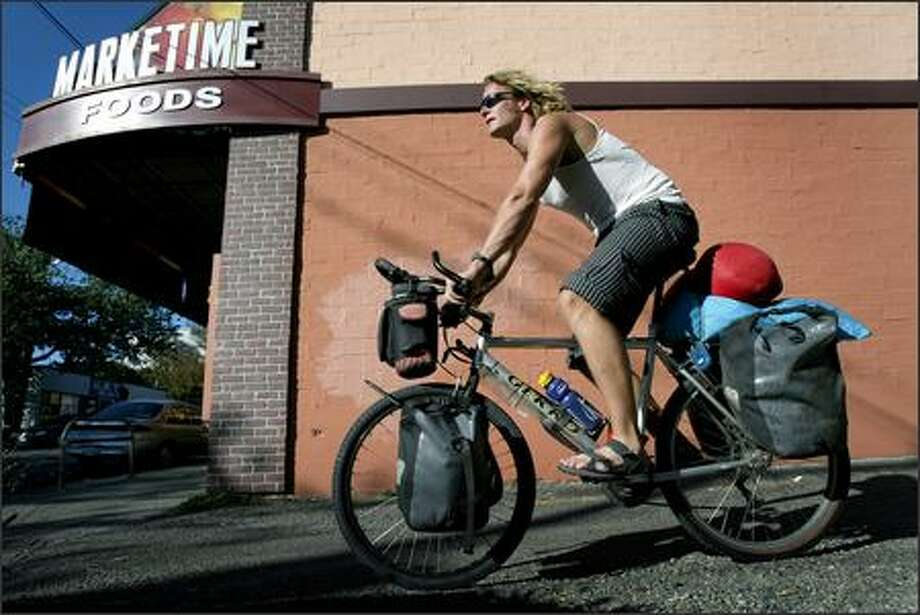 Rune Monstad of Norway, who is cycling around the world, is shown in a Fremont alley on Thursday near the spot where his passport and money were stolen earlier in the week.  Seattleites reached out to help him. Photo: Joshua Trujillo, Seattlepi.com / seattlepi.com