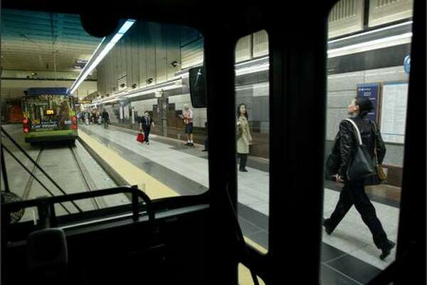 A rider jogs to catch her bus in the University Street Station as riders had to figure out where to catch their bus, and which direction it was headed, as the downtown transit bus tunnel reopened for weekday commuters.