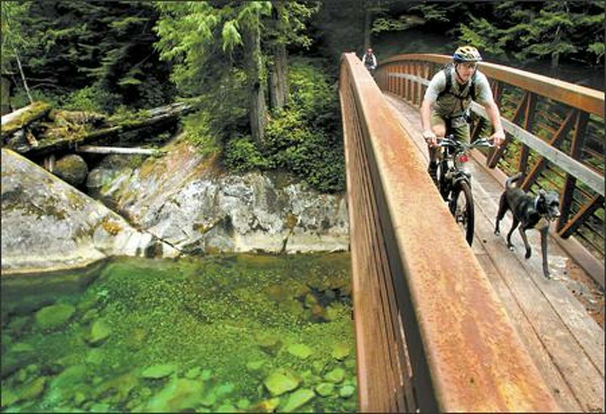 Backcountry Bicycle Trails Club president Brian Jones rolls across the Middle Fork Snoqualmie River with his dog Boomerang. The route is open to bikes on odd-numbered days through October.