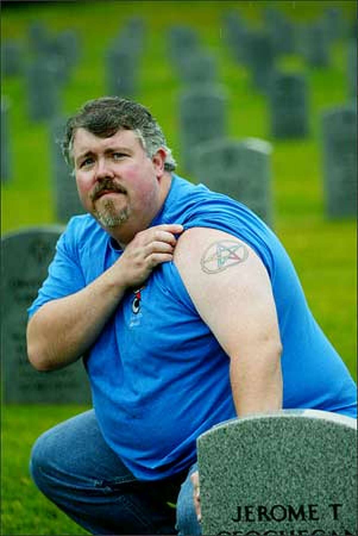 Scott Stearns, a Navy veteran, shows his pentacle tattoo while visiting Tahoma National Cemetery in Covington. He says the Defense Department doesn't allow the Wiccan pentacle on headstones. (