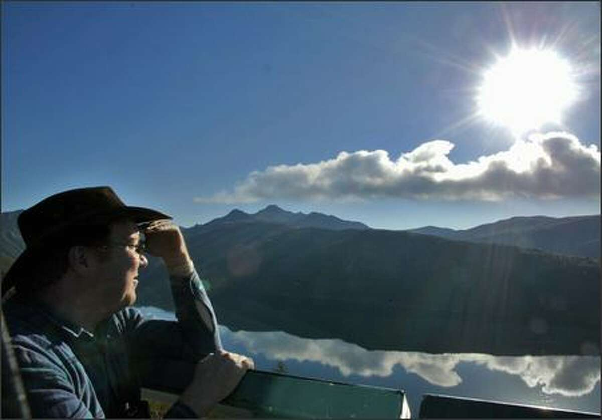Birch Frost of Seattle watches the morning steam eruption of Mount St. Helens from the Coldwater Ridge Visitor Center.