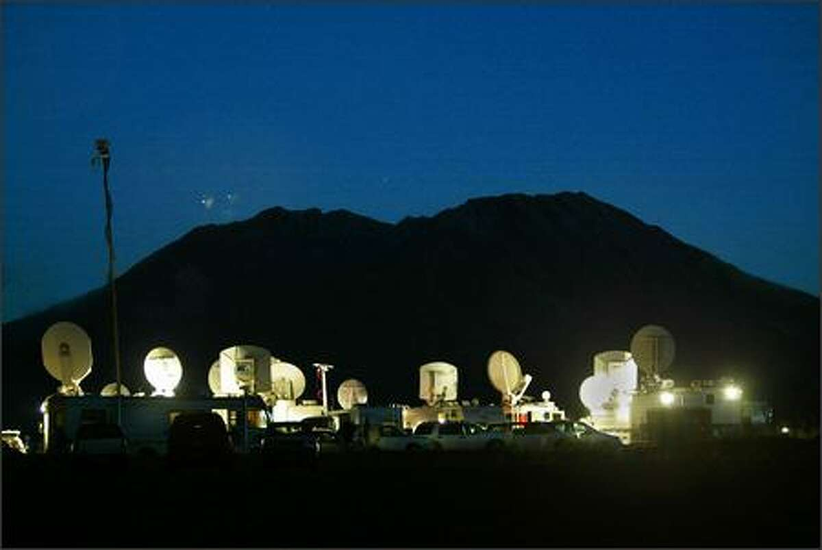 At the Castle Lake viewpoint, nine miles from Mount St. Helens, television satellite trucks light up the night on Monday as camera operators wait for activity. At 9:03 a.m. yesterday, they got it.