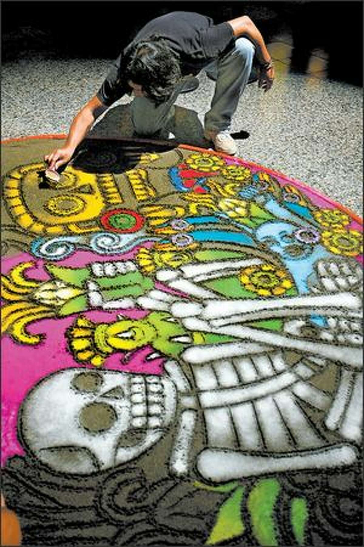 Mexican-born Seattle artist Isaac Hernandez Ruiz works on his sand painting depicting the circle of life. The Burke Museum commissioned the artist to create the painting and an altar to complement its