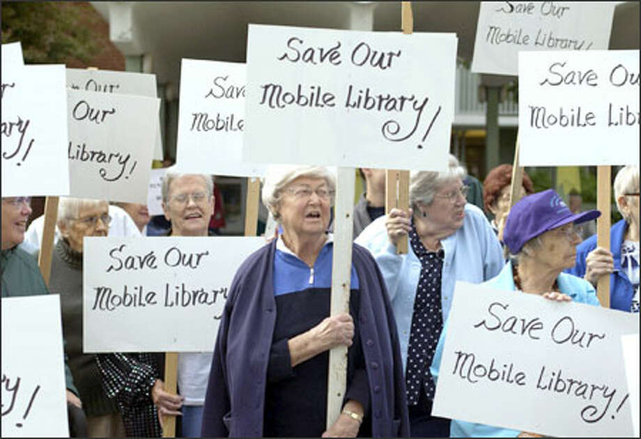 About 30 senior citizens, including Joyce Cheever, center, protest in North Seattle the proposed elimination of the Seattle Public Library bookmobile service.  The service circulates about 113,200 books and music recordings annually to retirement homes, child care centers and the homebound. Facing a budget crunch, the library has proposed ending the service; the library board thinks it can save about $800,000 next year by doing so. Photo: Ron Wurzer, Seattle Post-Intelligencer / Seattle Post-Intelligencer