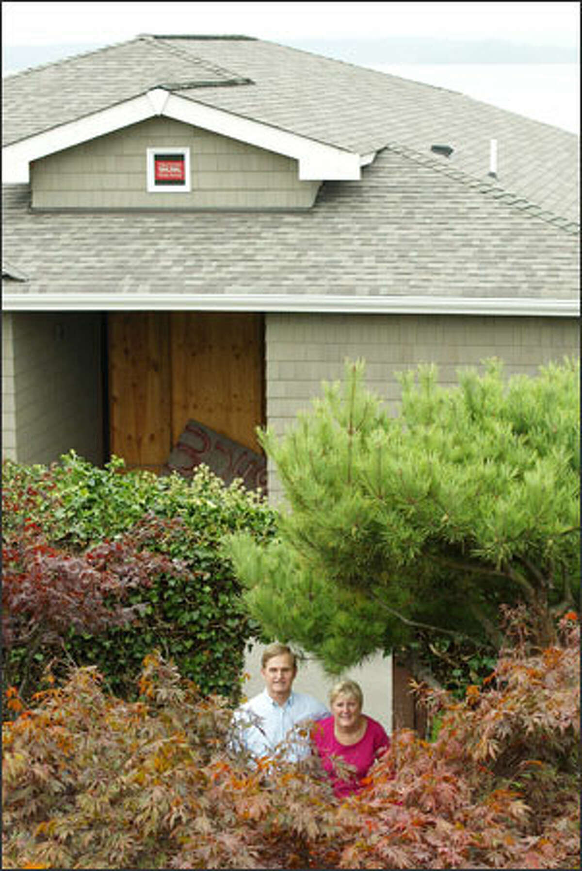 Dave and Carole Bauman, shown in their back yard in West Seattle Friday, won a legal battle when a judge told neighbors who own the house in the background to put a flat roof on it.