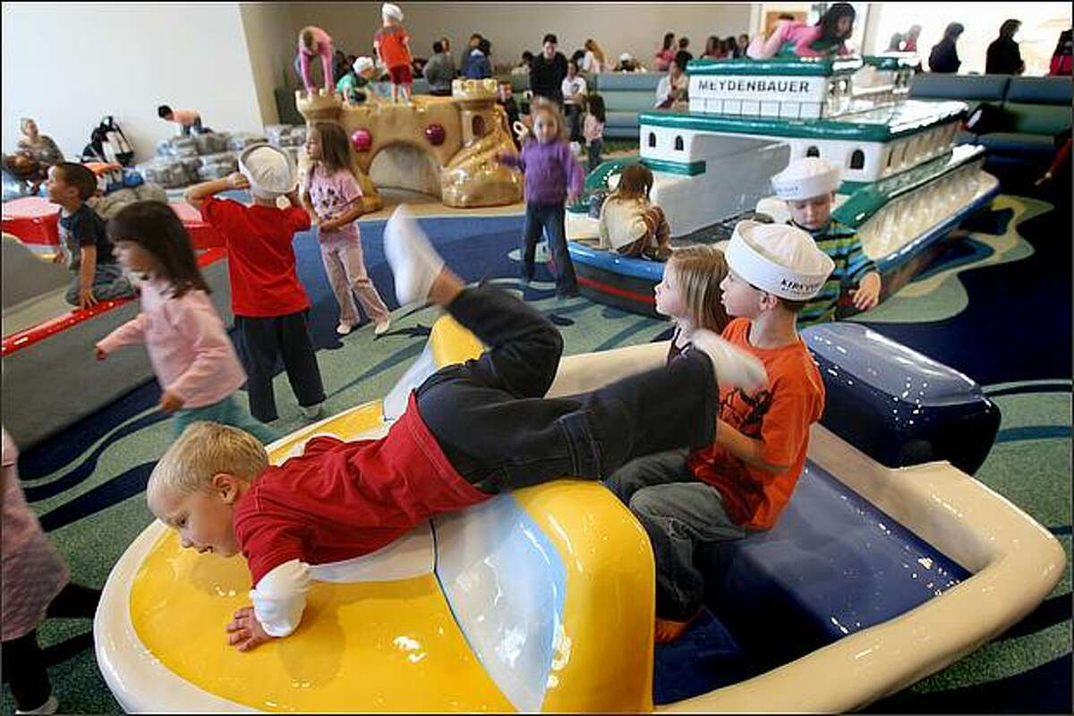 Ray Barry,4, from Redmond, Wash. (center bottom) plays on a make believe speed boat during the opening of Kids' Cove at Bellevue Square on October 10, 2008. (Karen Ducey/ Seattle Post-Intelligencer)