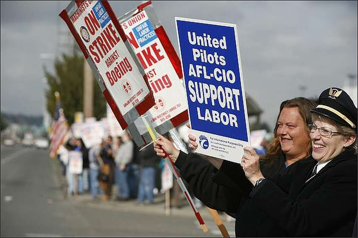 Cindy Reverstein, United Airlines first officer, right, joined Deanna Groom, a 10-year machinist from the Boeing Renton plant, as Reverstein and other union airlines employees joined striking Boeing machinists on the picket line at Gate 39 at Boeing Field on Thursday, October 9, 2008. (Paul Joseph Brown/Seattle P-I)