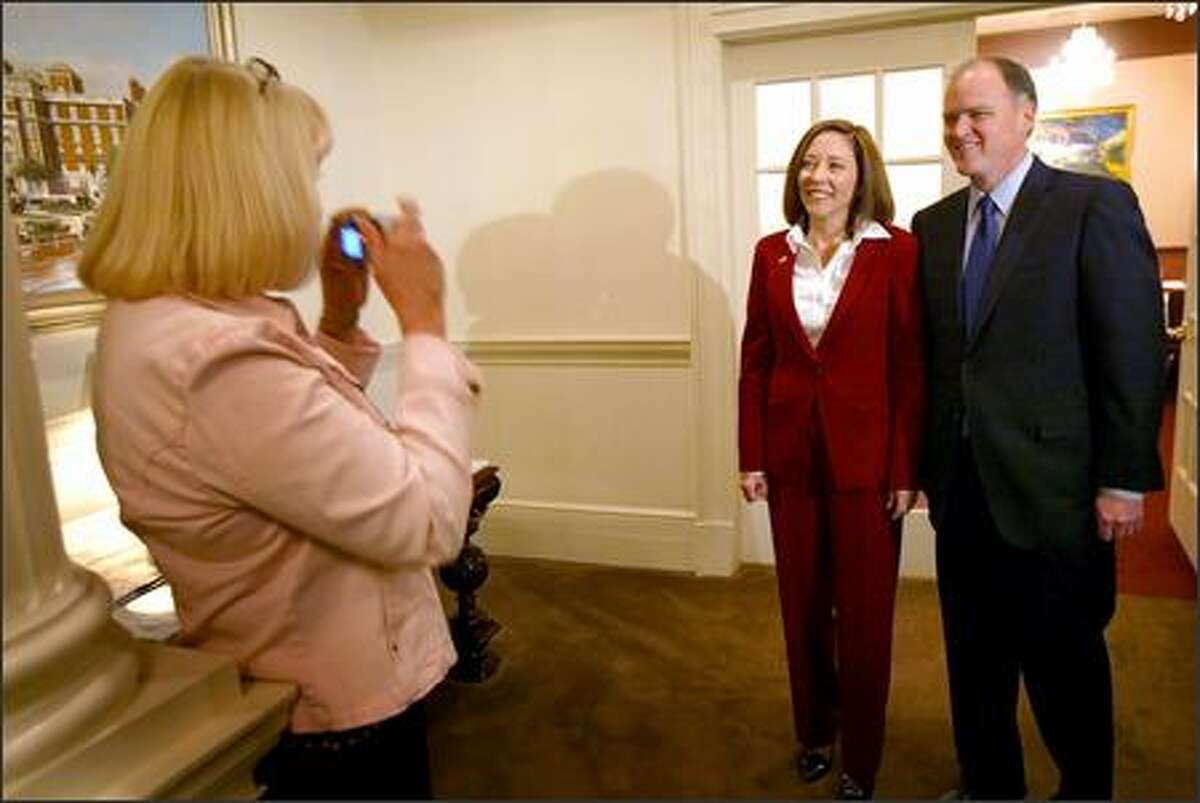 Democratic Sen. Maria Cantwell and Republican rival Mike McGavick pose for Robin Fontaine of Spokane before facing off in a debate on Thursday.