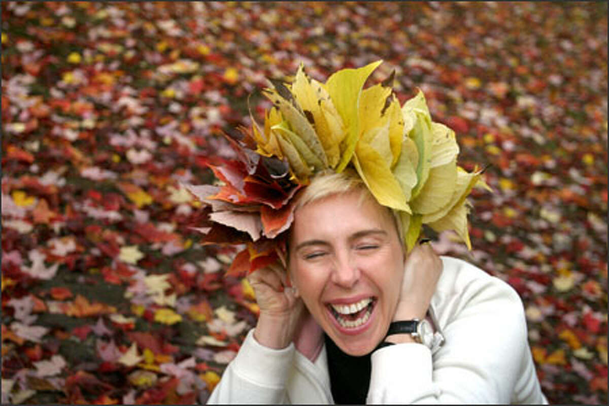 Natalia Gugel shows off an autumnal wreath at the Washington Park Arboretum in Seattle while posing for photos by Bud Marrese. Gugel said she learned the leaf-weaving technique in her native Ukraine. During the spring she likes to pick dandelions and weave them into similar wreaths.