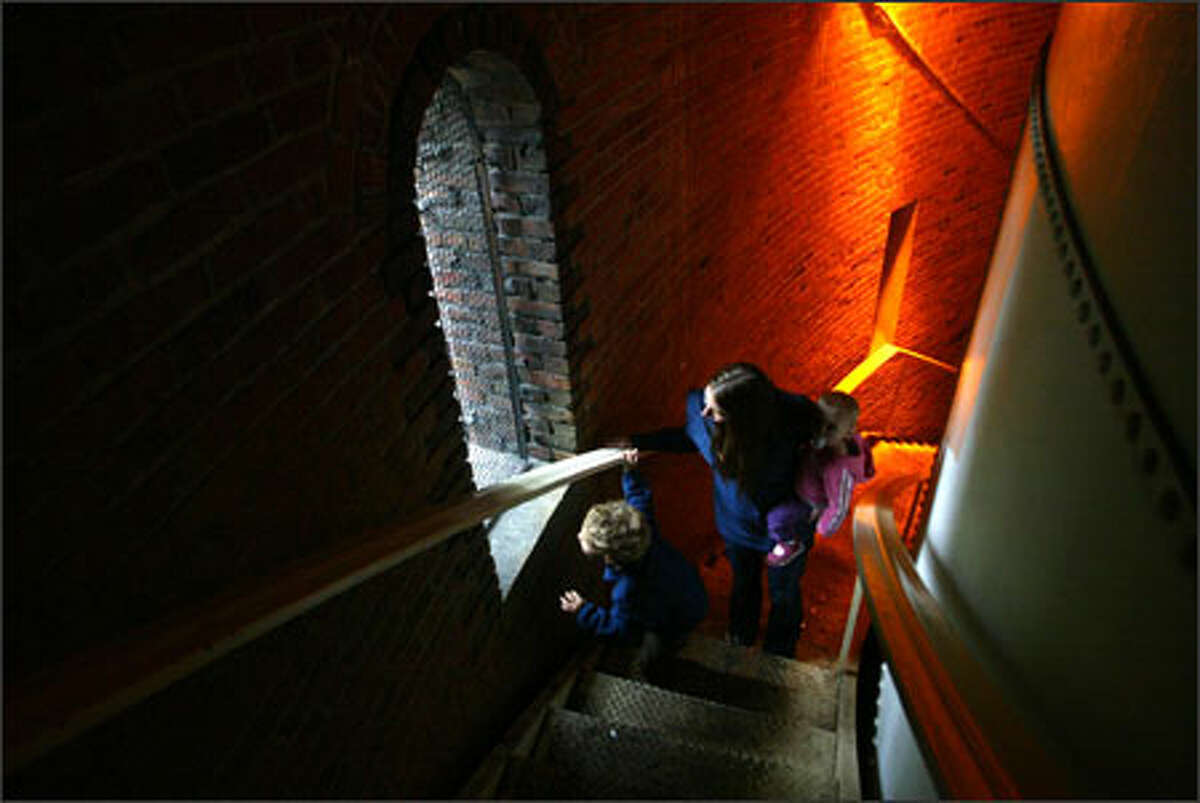 Nanny Carolann Streett and her charges, 4-year-old Carter Staley and 18-month-old Ella Staley, all of West Seattle, check out the view from the water tower staircase in Volunteer Park. Streett noted that it's nice to go to the parks when