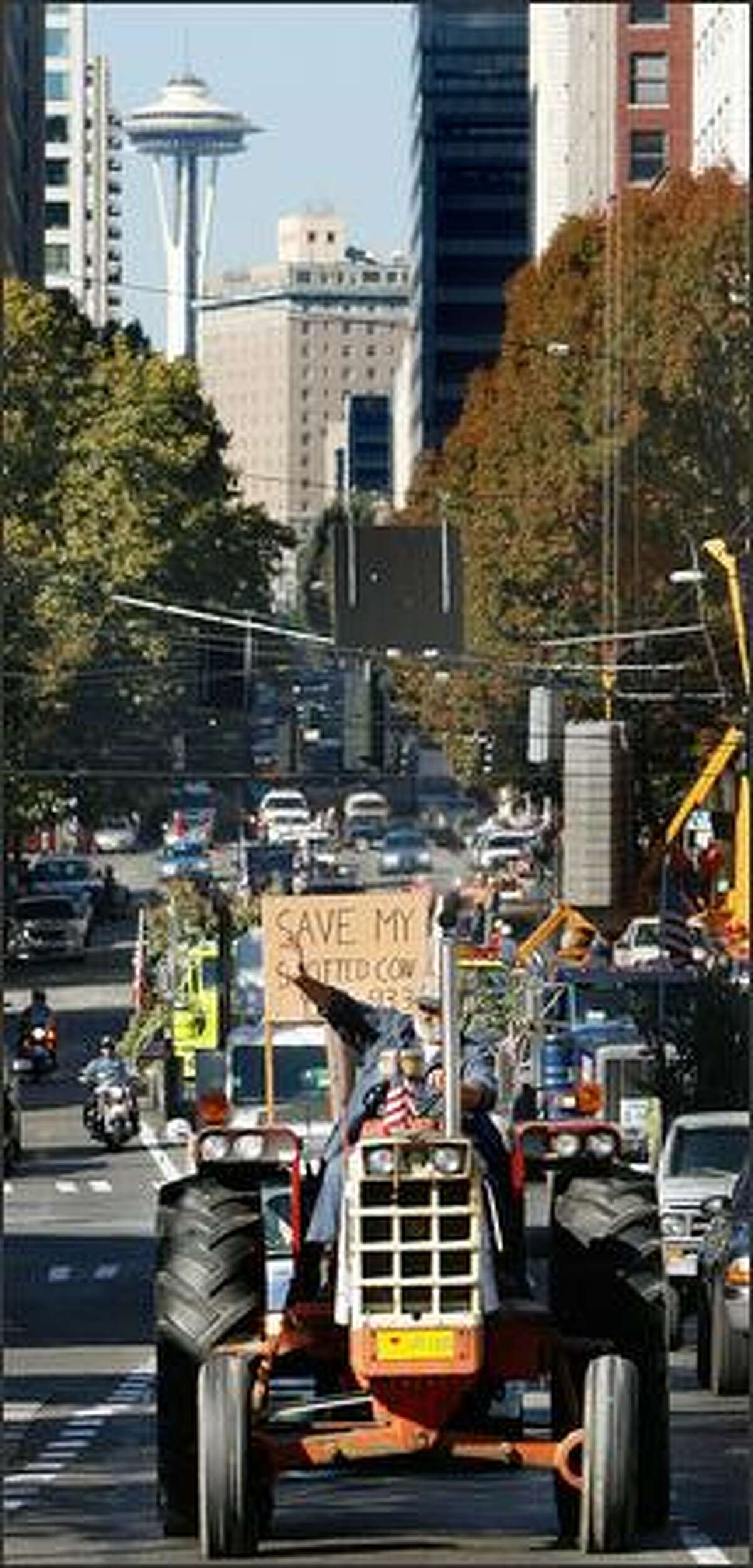 Whatcom County beef farmer Wes Kentch drives his tractor in a convoy with other I-933 supporters Thursday on Second Avenue in downtown Seattle. I-933 is a controversial land-use initiative being backed by many farm groups.