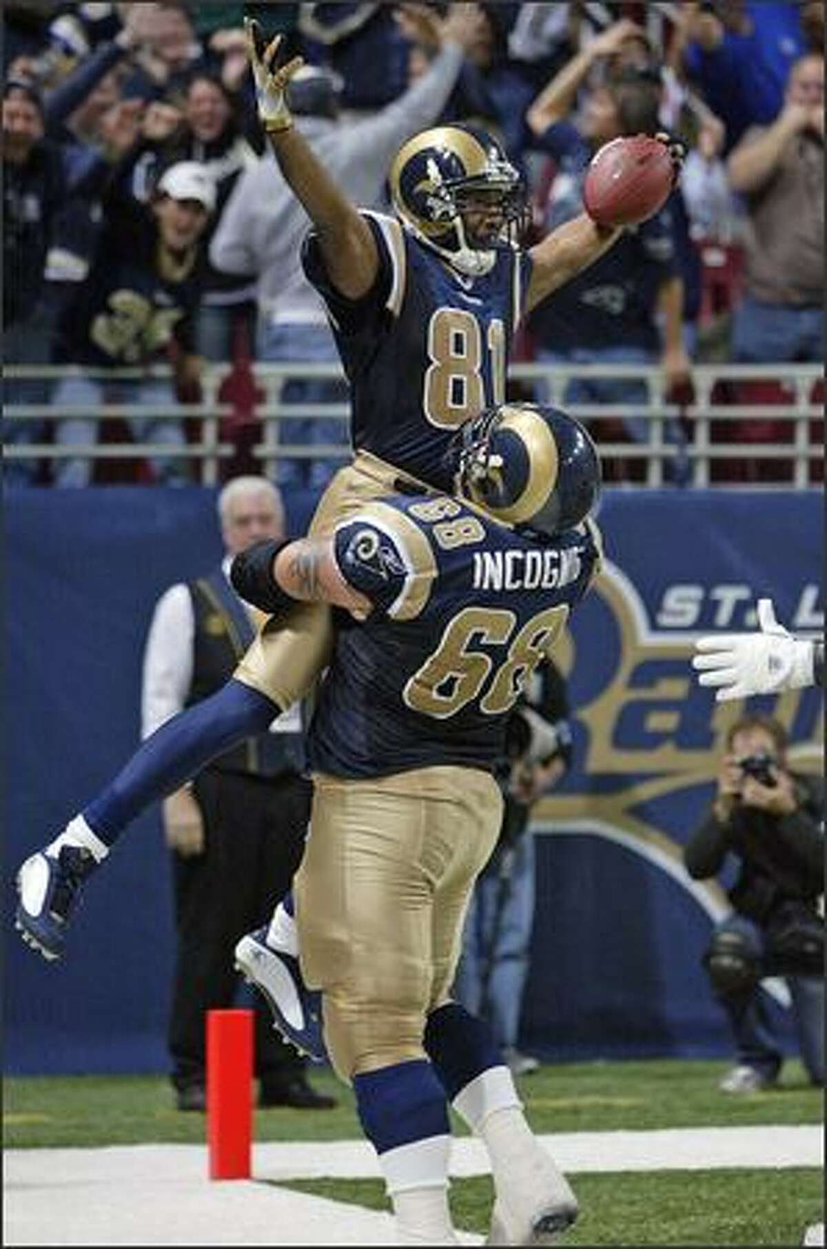 St. Louis Rams Torry Holt is lifted by teammate Richie Incognito after scoring the go-ahead 67 yard touchdown against the Seattle Seahawks during the fourth quarter of last Sunday's game -- which the Seahawks ended up winning 30-28.