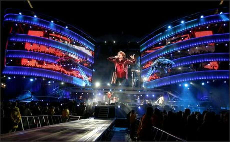 "Mick Jagger is dwarfed by his image on the big screen and by the huge set during the Rolling Stones' Qwest Field show Tuesday night.  Two multilevel structures, standing nearly seven stories high,  flank a 2,450-square-foot ""video wall."" Photo: Grant M. Haller, Seattle Post-Intelligencer / Seattle Post-Intelligencer"