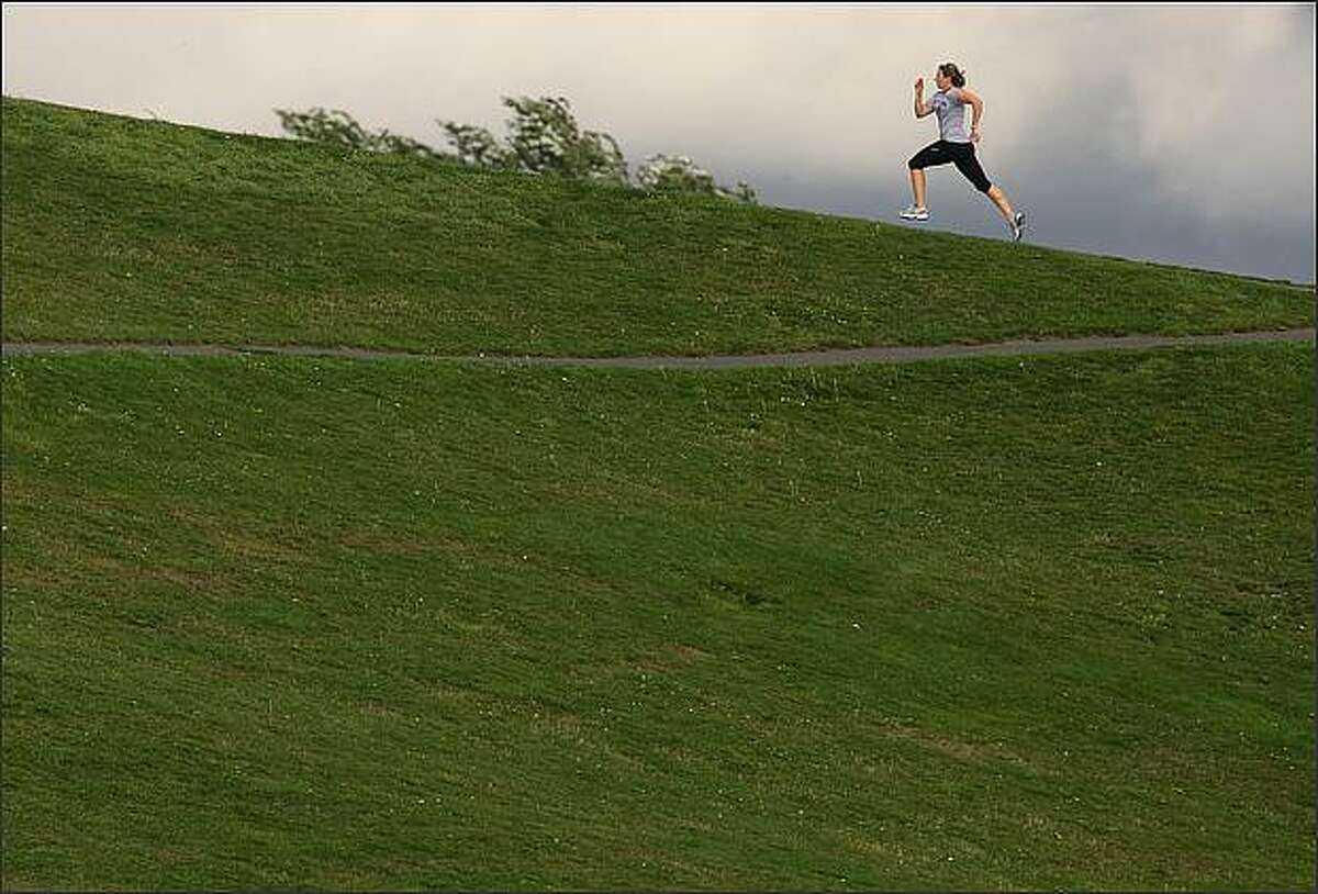 A brief flash of sun lights a runner as she sprints up a paved path at Gasworks Park.