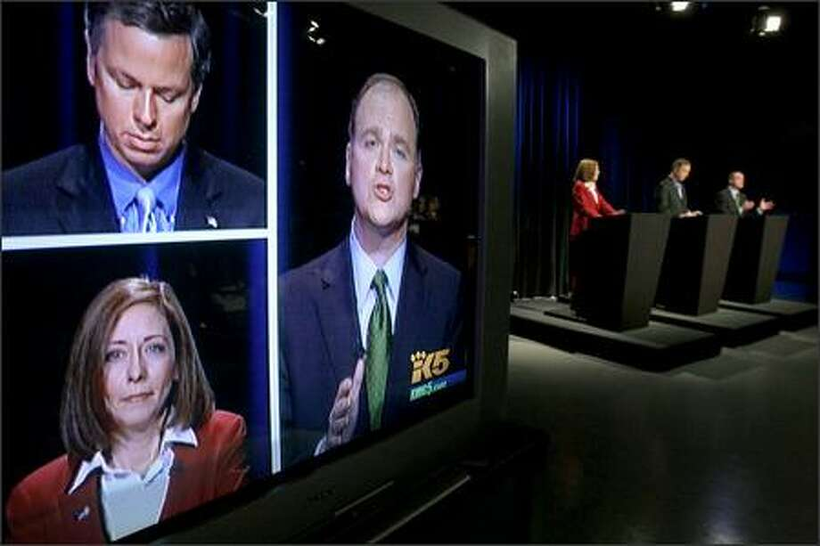 Libertarian Bruce Guthrie, top left, Sen. Maria Cantwell and Republican Mike McGavick are shown on a screen Tuesday for the live audience at a Senate debate at the KING/5 studio in Seattle. Photo: Meryl Schenker, Seattle Post-Intelligencer / Seattle Post-Intelligencer