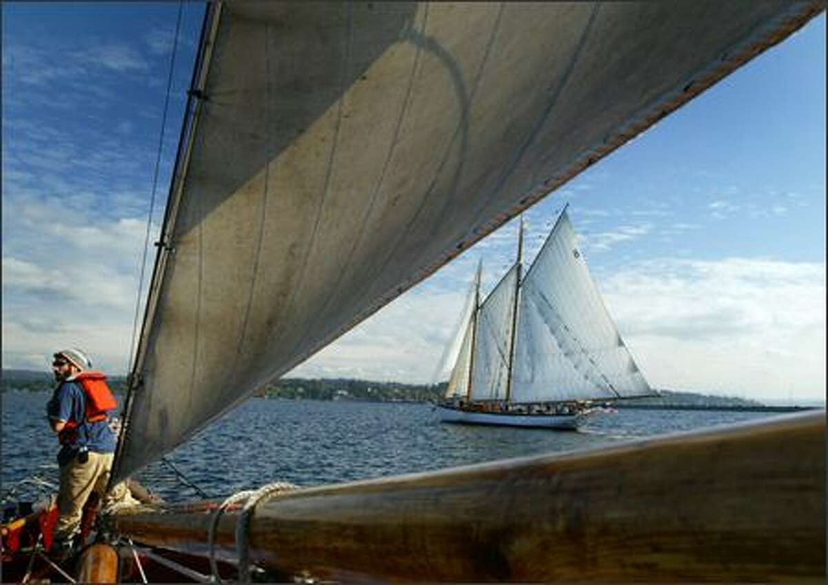 Crewmember David Gelman is on bow watch duty as the 136-foot historic schooner Adventuress sails on Lake Washington alongside the 164-foot schooner Zodiac. The sail was a reunion of sorts for the two historic gaff-rigged ships. The two were built in East Bothbay, Maine -Adventuress in 1913 and Zodiac in 1924.
