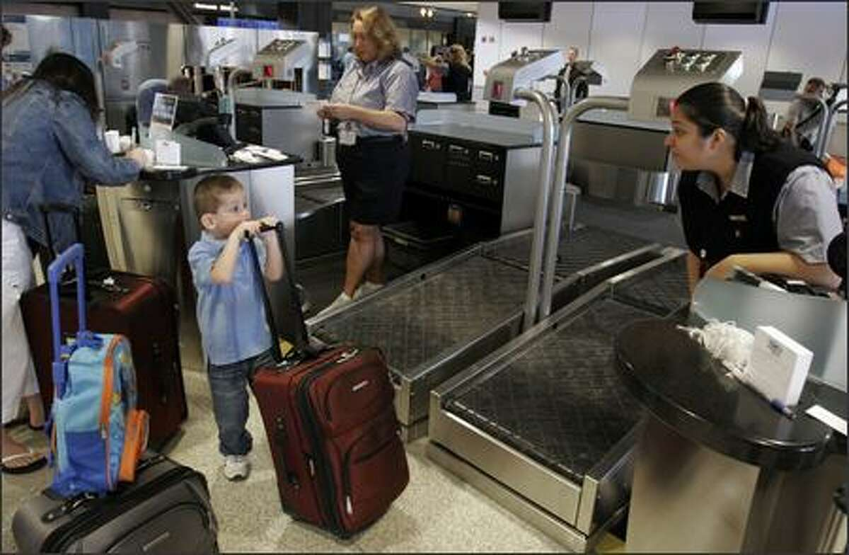 Alaska Airlines customer service agent Cheryl Canchola, right, speaks with Jaxon Mayer,4, of Arlington, as his parents, Jennifer and John Mayer check their bags for a trip to Disneyland using the new system at Sea-Tac Airport. Hollis Lovelace, rear, helps the Mayer family. The new system replaces the traditional ticket counter with islands.