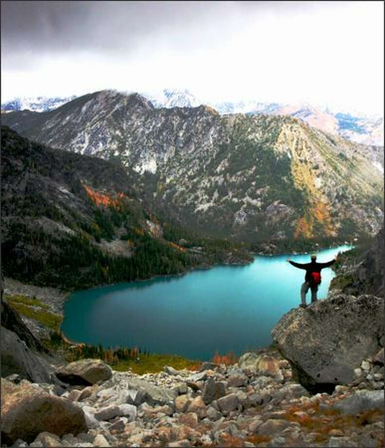 """A hiker takes in the sights of Colchuck Lake from the top of Aasgard Pass on the way to Enchantment Lakes Basin. Just 24 people are permitted to enter the """"core"""" Enchantment area each day. Sixteen are chosen by advance lottery, eight more by walk-in lottery. Camping at Colchuck is limited to three groups a day. Photo: Joshua Trujillo, Seattlepi.com / seattlepi.com"""