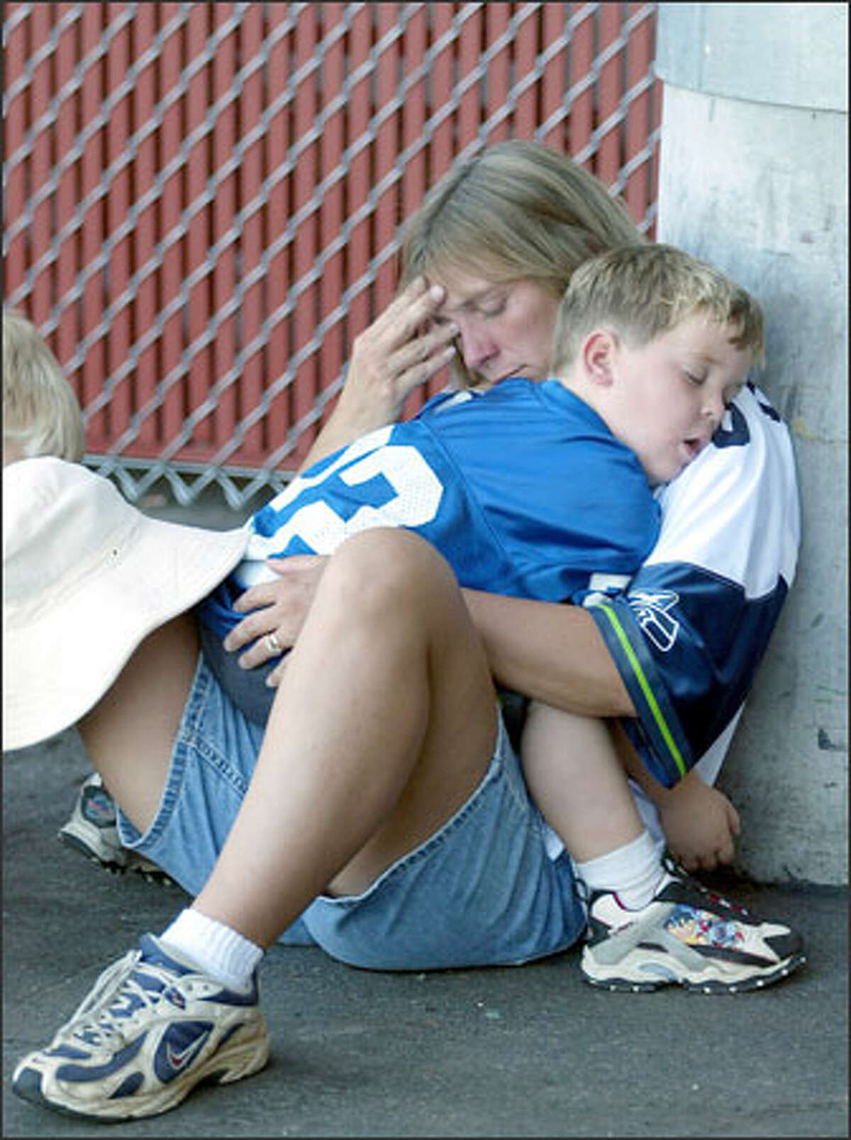 Seahawks fans Kim Rucker and son Jared Rucker from Athens, Tenn., try to sleep off a disappointing afternoon.