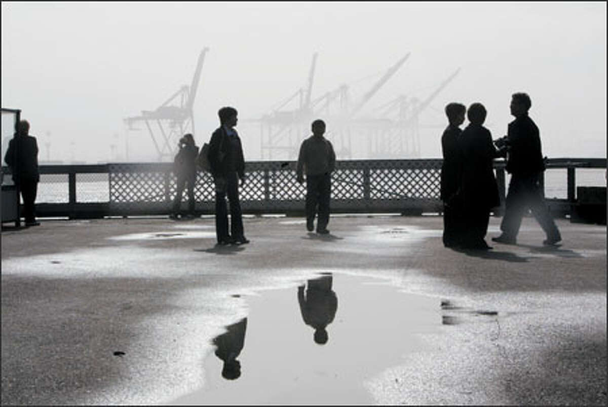 """Tourists check the limited view of the Seattle waterfront from Pier 57 on a foggy day. Michael Nguyen of Chicago, with the group on the right, said: """"It's very nice to be here. I think this weather is perfect."""""""