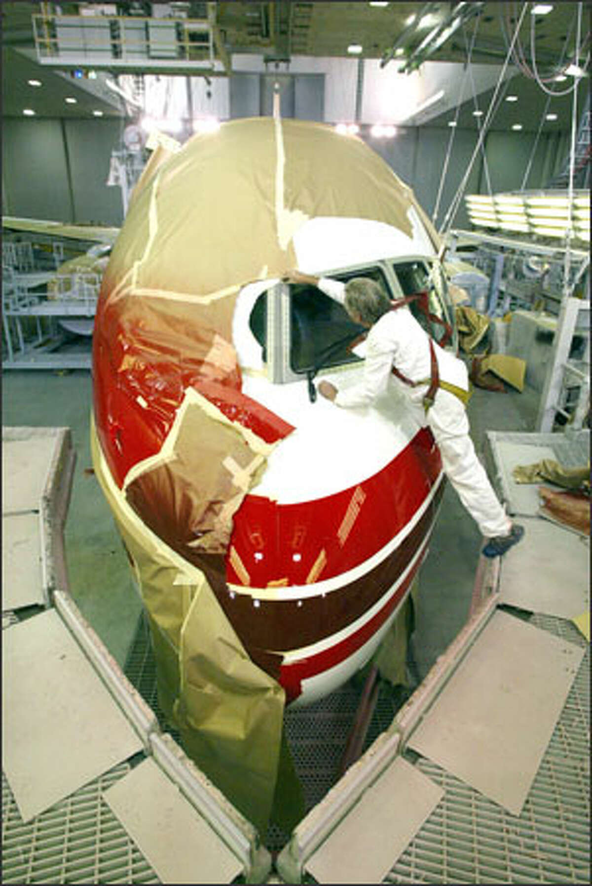 Al Ystad removes masking tape from around the windshield of the last Boeing 757 in the paint factory at the Renton plant. The plane is set to be rolled out this week and will be delivered to Shanghai Airlines in April.